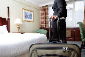 Woman standing with baggage in hotel room